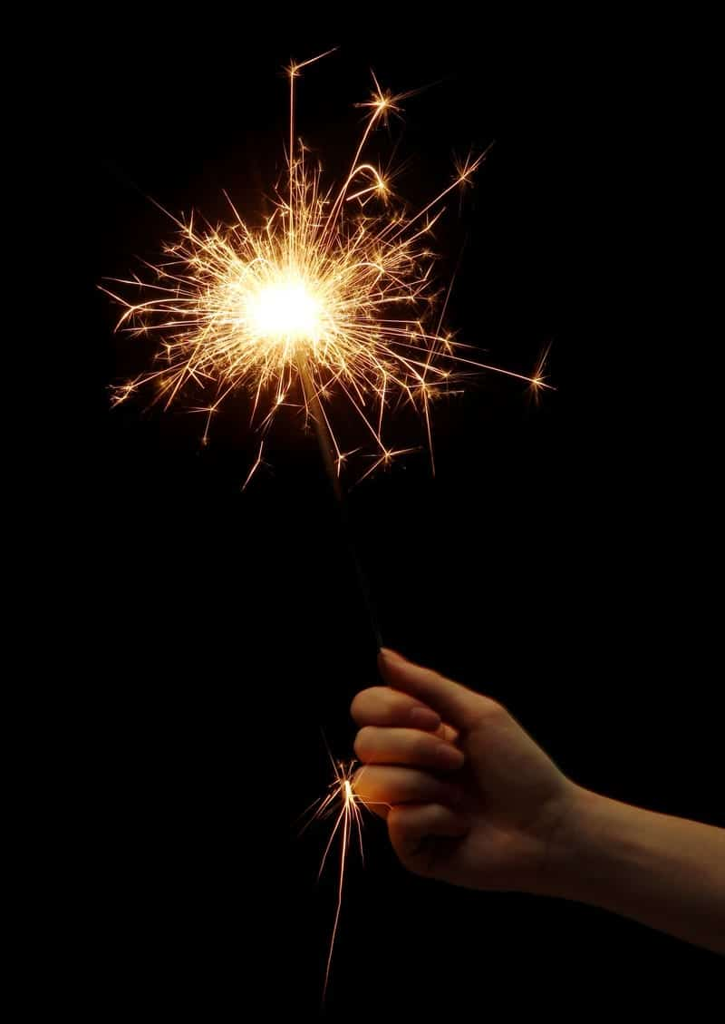 Close up of a sparkler in someone's hand with a black background