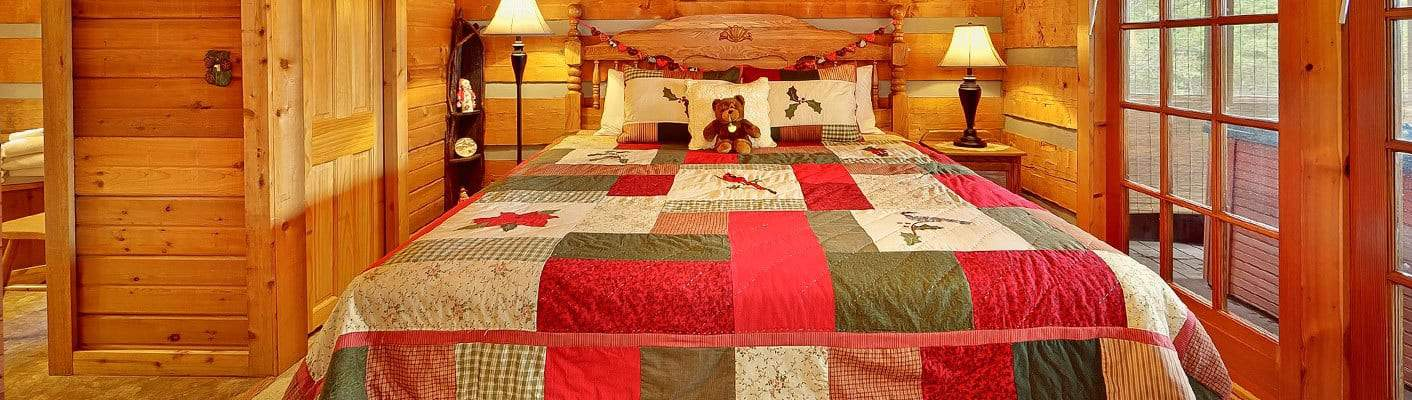 The bedroom in a Smoky Mountain cabin rental with a luxurious Queen bed, teddy bear, and charming hardwood decor.