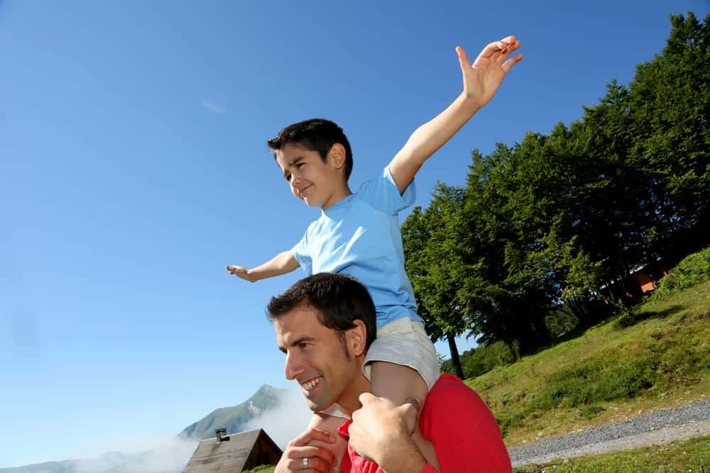 A father giving his son a piggyback ride in the mountains.